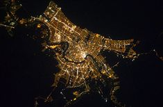 New Orleans at night as seen from space orbit. The Gulf of Mexico is the dark area in the upper portions of the frame. The Mississippi River is visible winding its way through the city toward the Gulf.  photo from the International Space Station, 2011.