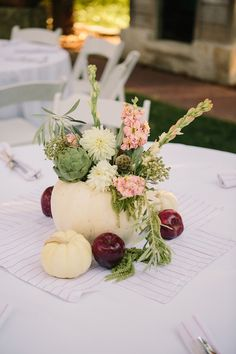 Centerpiece arrangement for rehearsal dinner in white cinderella pumpkin with stock, dahlia, tuberose, artichoke, olive. Photo by Matt Edge Photography.