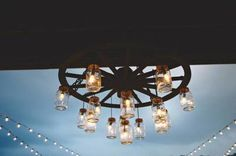 A chandelier made out of a wagon wheel and mason jars #countrywedding #rusticweddingdecor http://www.greatamericancountry.com/living/lifestyles/country-wedding-decor-pictures?soc=pinterest