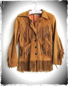 """Badass 1970's jacket!  Buttery soft suede with fringe and stunning hand woven details in front and back!   Two front patch pockets with scalloped edges.  Button front closures.  Fully lined. Well worn for a true vintage feel with most signs of wear on shoulder, sleeve opening, and neckline. Spotting all over.Made by Pioneer WearNo marked sz, recommended for sz XS/SMeasurements taken buttoned and lying flat:Shoulder 17""""Bust 36""""Waist 33""""HIp 35""""..."""