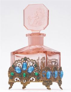 HOFFMAN (Czech) Perfume bottle in pink crystal with enameled and jeweled metalwork on four sides, cupid and Psyche stopper with dauber stub, 1920s. Intaglio HOFFMAN mark.