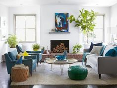 This living room features blue accents like the blue bird paper weight and the blue armchairs. A single emerald green pouf provides another pop of color.