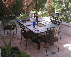 A wrought iron patio dining set placed on a front patio of a home allows its owners to visit with neighbors and passers-by.