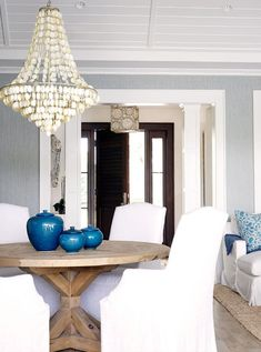 The ultimate beach house dining area  white slipcovered chairs, shell chandelier, blue accents