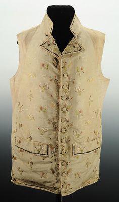 Gilet boutonnant droit au moyen de 11 boutons en bois recouvert de drap,entièrement en drap blanc richement brodé en fils de soie de couleur de fleurs mélangées à des drapeaux tricolores, le col les poches et lensemble du gilet est bordé dune suite de sequins dargent.