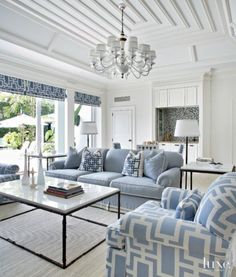 Crisp white and strong geometric details on the ceiling and cabinetry, not to mention fabric from Clarence House on the chairs, mark the loggia. The glass tiles in the bar area, from Artistic Tile, echo the spectrum of blues in the pool beyond. Another carpet from Stark underscores the space.