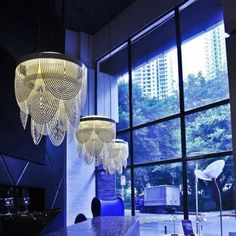 The Ceremony chandelier by Slamp was designed by Bruno Rainaldi. This contemporary chandelier is made from an opalflex material. The Ceremony chandelier is made up of white swags of opalflex which lets the light illuminate through the openings c.