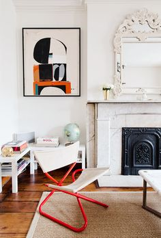 White walls, graphic wall art, white fireplace, white framed mirror, beige rug, red chair, and white shelves