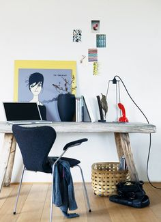 The weathered wood desk adds a softness to the modern design of the space. #desk #studio #artwork #simple #modern