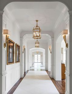 A long hallway features walls clad in wainscoting lined with kids' photos in gold baroque frames illuminated by antique brass sconces, Ruhlmann Single Sconces, as well as round brass lanterns, Round Edwardian Entry Lanterns. Design Entrée, Flur Design, House Design, Lobby Design, Design Ideas, Hallway Chandelier, Hallway Lighting, Hallway Sconces, Hallway Ceiling