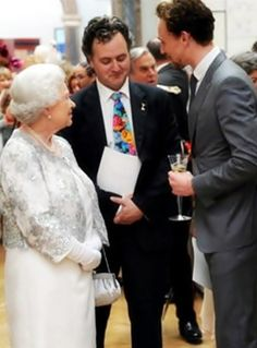 Even the Queen looks lost in Tom's glow.