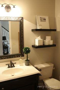 floating shelves from ikea over toilet for storage and decoration pretty mirror over the sink pretty to add flowers of pictures
