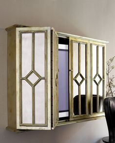 """Flat-Screen TV Entertainment Wall Cabinet at Horchow.  Made of antiqued mirror glass and antiqued silver-finished wood. Accommodates up to 50"""" TV. 54""""W x 11""""D x 40""""T. Interior measures 50""""W x 7""""D x 36""""T."""