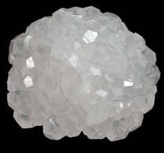A strange, strange calcite // Hemispherical formation of lustrous translucent colorless calcite crystals with no matrix attached. The calcite crystals are hexagonal form with rhombohedral terminations and they fluoresce orange under UV illumination.