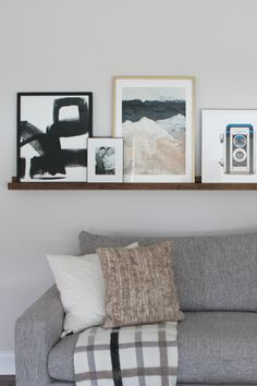 Diy Picture Ledge Over The Couch Filled With Art