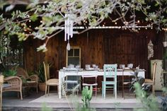 backyard dinner party with mix and match chairs + cafe lights + vintage dishware