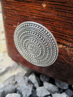 Silver door knob.  http://www.etsy.com/listing/80854899/metal-disc-drawer-knob-with-circle