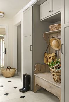 Mudroom: black and white tile, sage green cabinets, wooden bench.