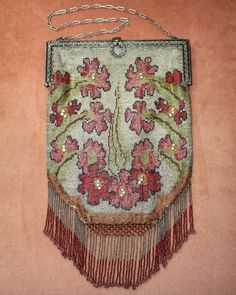 """Lovely French c1920s cut steel purse done in shades of pink, red, yellow, green brown, copper and silver. It's a pretty design of flowers and leaves with a few bezel set rhinestones in the body of the purse. It measures 11 1/2"""" long, including the fringe by 6 1/2"""" wide."""