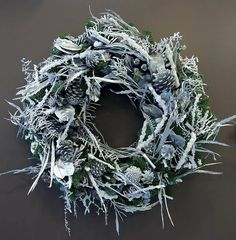 Natural frosted Christmas wreath - with pine cones and dried leaves and twigs. Design by Phillo Flowers in Notting Hill, West London