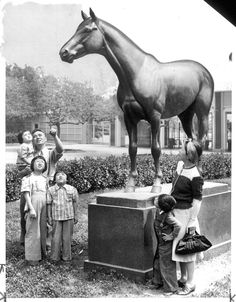 """Seabiscuit's Statue Interests Japanese -- Y. Akasaki and his family inspect the statue of Seabiscuit after they arrived at the Santa Anita race track, recently converted into an assembly center for evacuated Japanese, April 3, 1942. They were among the first contingent of evacuees to be quartered at the big racing plant.""--caption on photograph. 1942-04-03. Publisher: University of Southern California. Library. Dept. of Special Collections. Regional History Collection."