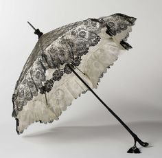 Parasol with machine-made lace canopy, Anonymous, c. 1890 - c. 1900  Parasols with a black lace canopy over a white silk ground had been in fashion since 1850and where therefore nothing new in the 1890s. Yet the maker of this parasol added an innovate element by decorating the inside of the canopy. When the opened parasol is carried over the shoulder, a border of black flowers surrounds the face.