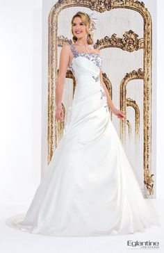 Robe de mariée drapée en satin avec décolleté orné de broderie. Jupe ouverte sur du tulle. Fermeture et boutonnage dos.