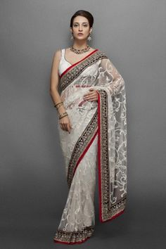 vory Sari with sequin jaal and black intricate border in kundan work  Availability: In stock    This ivory sari comes with a sequence jaal in the centre. It has a black border of ethnic kundan embroidery with red piping.