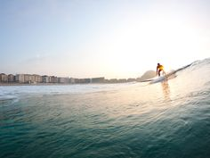 Photo: A surfer rides a wave at sunset in San Sebastian, Spain