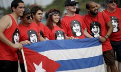 Fans hold a Cuban flag outside Ciudad Deportiva de la Habana sports complex where the Rolling Stones' free outdoor concert will take place today in Havana