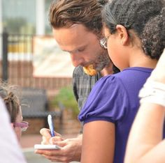 Andrew Lincoln signing autographs with a nugget in his mouth.