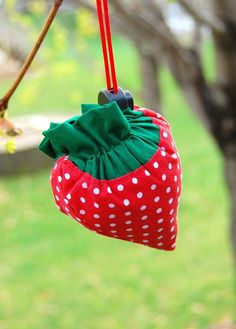Instructions for how to make a tote bag that folds up into a strawberry shape.