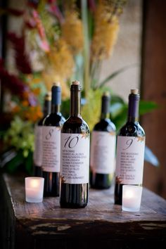 Wine bottle table numbers with list of guests at table.    colorful tropical wedding at the Kampong, photos by Maloman Photographers | via junebugweddings.com