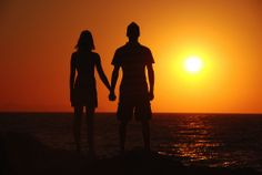 A couple watching the sunset on a beach in Greece
