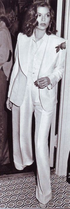 Bianca Jagger in a white pantsuit on a DAVID HICKS carpet.