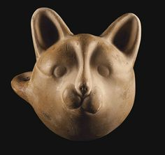 AN ANATOLIAN POTTERY MUG   Circa 1800-1600 B.C.   In the form of a cat head, naturalistically rendered with erect ears, small circular eyes and a projecting muzzle, concave on the interior, a loop handle at the side  4¼ in. (10.8 cm.) long
