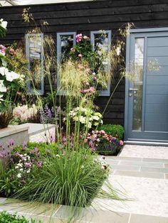 blühende Blumen und Ziergräser im Kontrast zur dunklen Fassade