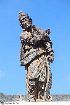 """Profeta Ezequiel EZEQUIEL:  Do lado oposto a Baruc, no pedestal que arremata o muro de alinhamento central do adro, encontra-se Ezequiel, também conhecido como o """"profeta do exílio"""", por ter sido banido para a Babilônia com o povo de Israel.  A inscrição do pergaminho traduz a síntese de três etapas sucessivas da visão do profeta: primeiramente, aparecem-lhe quatro animais alados de quatro faces cada um, em seguida, as quatro rodas de um carro de fogo sustentando um trono de safira e…"""