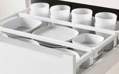 Открытый ящик в кухне ИКЕА крупным планом. Белая столовая посуда, разделенная разделителями для ящика