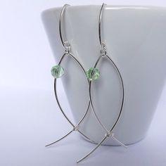 brincos em formato de peixe em fio de prata com olhinhos de cristal verde
