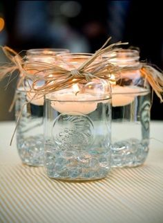 Mason jar centerpieces with floating candles. [UPDATED These DIY Mason Jar Centerpieces can also be made into favors. Use the lanterns to provide light to your wedding tables. Floating Candle Centerpieces, Rustic Wedding Centerpieces, Diy Centerpieces, Jar Candles, Round Candles, Quinceanera Centerpieces, Ideas Candles, Wedding Tables, Easy Table Decorations