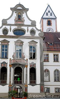 Photo made in the town of Fussen in Bavaria (Germany). The picture shows the nput and the facade with large windows and decorated, in a beautiful building in the city center. To the right of the elegant building you are also seen the portion of an other house dominated by the clock tower.