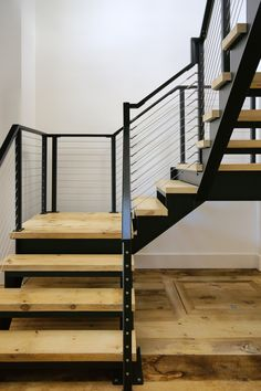 These steel stair stringers are made from laser cut steel. The cross section of the stringers are a stepped I-beam shape. Treads are antique pine. The wood top rail is painted black. Cable railings were employed on the stairs and balcony. Cable Stair Railing, Black Stair Railing, Staircase Handrail, Steel Handrail, Steel Stairs, Staircase Design, Stair Risers, Outdoor Handrail, Iron Staircase