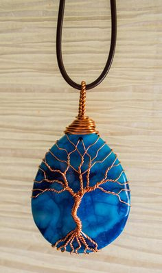 Tree of Life wire wrapped around a blue stone pendant . Pendant is 2 inchs in length. All wire used in making this pendant is recycled copper (see details below). Drop ring incorporated into wire wrapping for easy use with a necklace of your choosing. Black cord necklace can be provided with pendant if specified in order.
