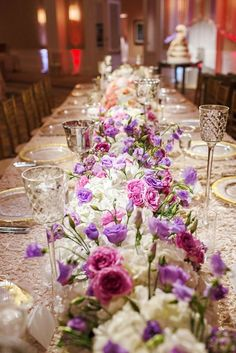 Breathtaking purple and pink wildflower wedding reception centerpiece with classic white flowers; Featured Photographer: Perez Weddings