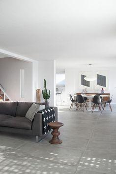 carrelage beton, grand sofa gris, table tulipe avec des chaises