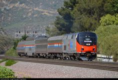 "A short Amtrak train, operated for Amtrak President Joseph Boardman, climbs southern California's Cajon Pass on May 30th, 2016. This train, comprised of P42DC 156 (wearing the Phase I scheme it received as one of the carrier's 40th Anniversary engines in 2011), sleeper 10021 ""Pacific Cape,"" Viewliner sleeper 62033, dome-lounge 10031 ""Ocean View"" and business car 10001 ""Beech Grove"", is operating from Los Angeles to Stockton, and the next day will continue on to Sacramento in order to…"