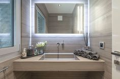Modern style bathroom vanity with backlit mirror. Baltina House by studiodonizelli