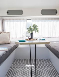 This cosy dining area is designed to fold away, transforming the seating area into a bed. #campermakeover  #holidayhome #camper  Photography by: Nicola Edmonds.