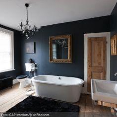 Klassische Elemente wie Kronleuchter in Antik-Optik und Spiegel mit Goldrahmen werden mit modernen, schlichten Sanitärobjekten kombiniert. Das Ganze findet auf Holzdielenboden mit kuscheligem schwarzen Teppich vor Wänden in Anthrazit statt. So entsteht ein klassisches Designer-Bad mit gemütlichem Flair.